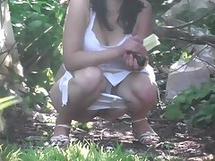Young girl peeing in the bushes